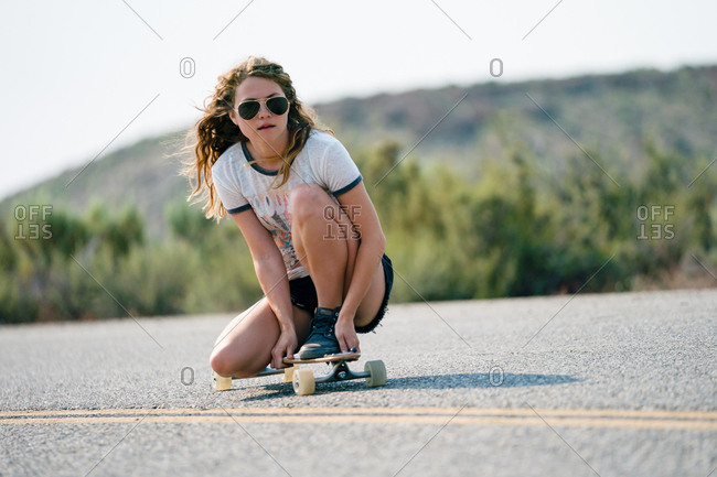 Woman Crouching On Skateboard
