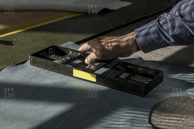 Person using molding machine on piece of leather