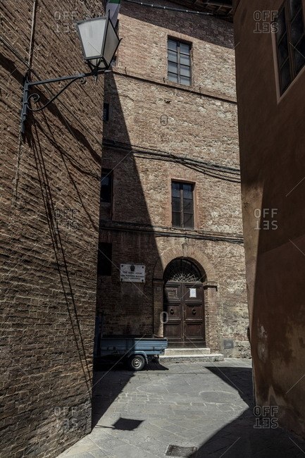 Siena, Italy - August 16, 2017: Brick buildings and narrow street