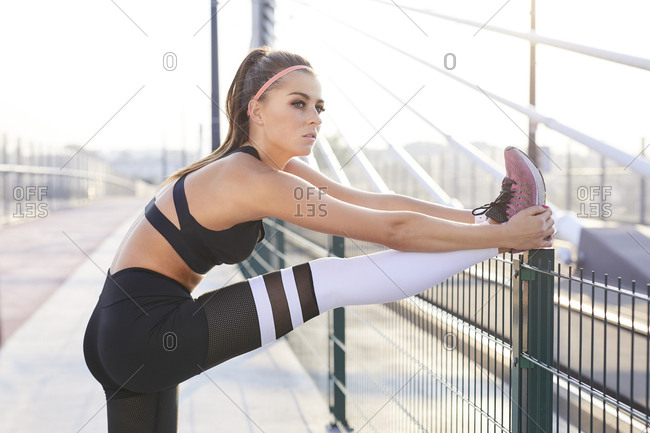 Young athletic woman stretching her legs after urban workout