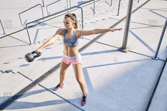Young woman doing kettlebell swing exercise outdoors