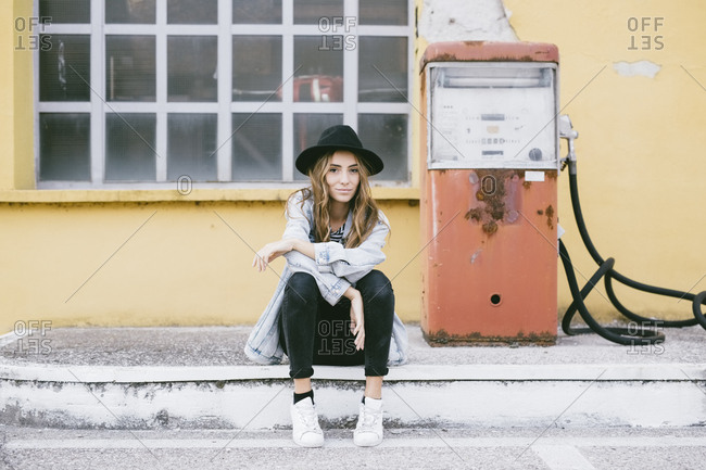 Portrait of fashionable young woman wearing hat sitting beside an old petrol pump