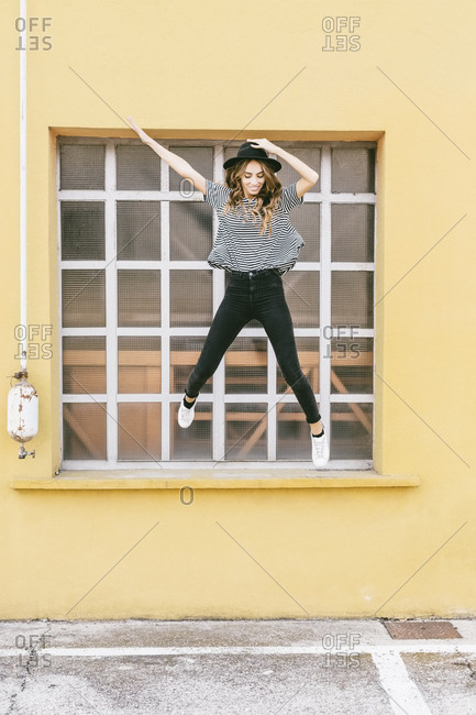 Fashionable young woman wearing hat jumping in the air