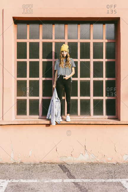 Fashionable young woman standing on window sill