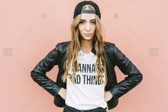 Portrait of fashionable young woman wearing black baseball cap and leather jacket