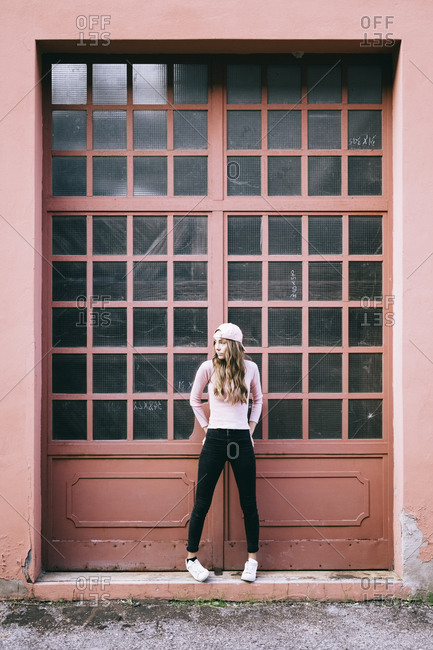 Fashionable young woman standing in front of entrance gate