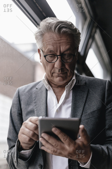 Businessman leaning on window- using digital tablet