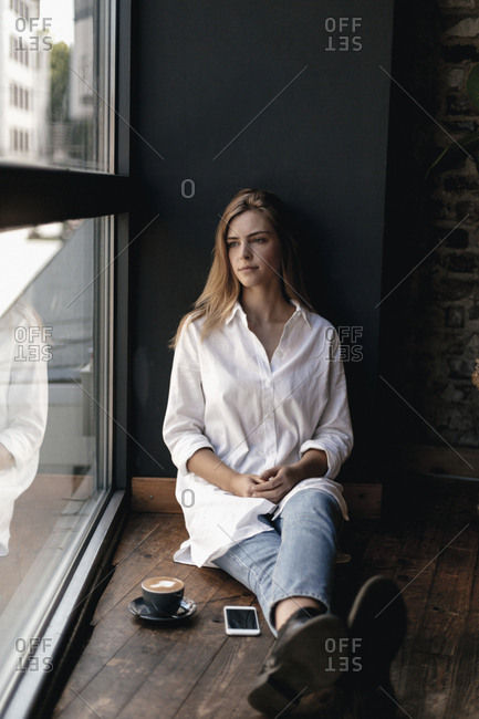 Young woman sitting on window sill in a cafe- looking out of window