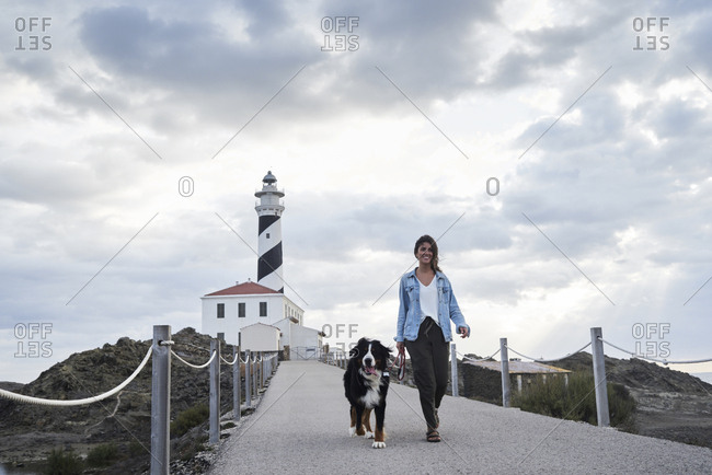 Spain- Menorca- Bernese mountain dog walking together with his owner outdoors at lighthouse