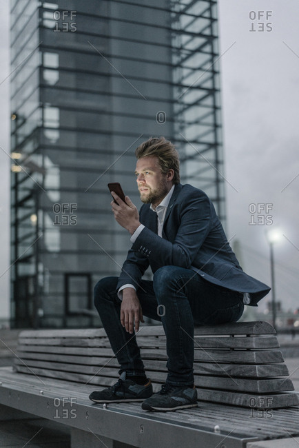 Businessman sitting on bench in the city holding cell phone