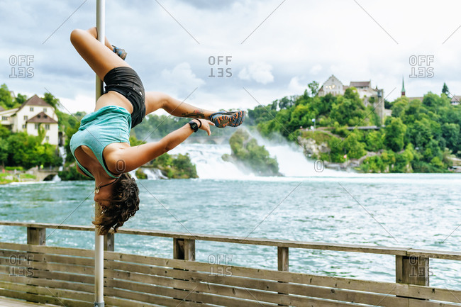 Switzerland- Schaffhausen- woman doing pole dance posture at the Rhine Falls
