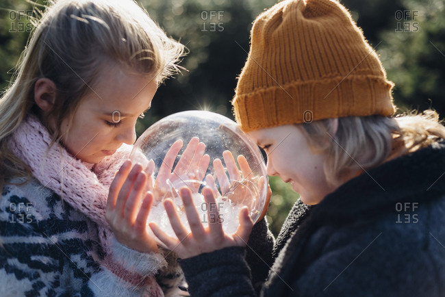 Brother and sister looking into crystal ball filled with snow- making a wish
