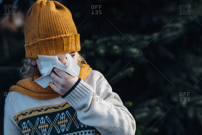 Little boy having a cold- blowing his nose