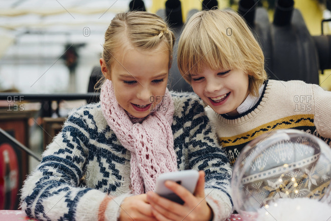 Brother and sister sending text messages with Christmas wishes on smartphone