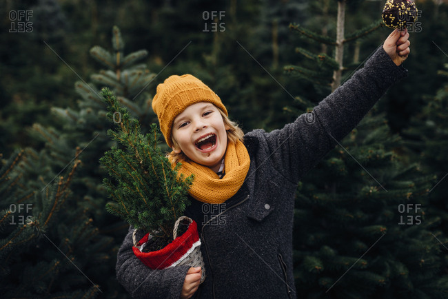 Happy boy preparing for Christmas - holding potted tree- eating chocolate dipped apple