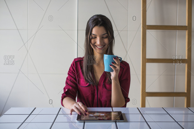 Woman looking at tablet computer and smiling