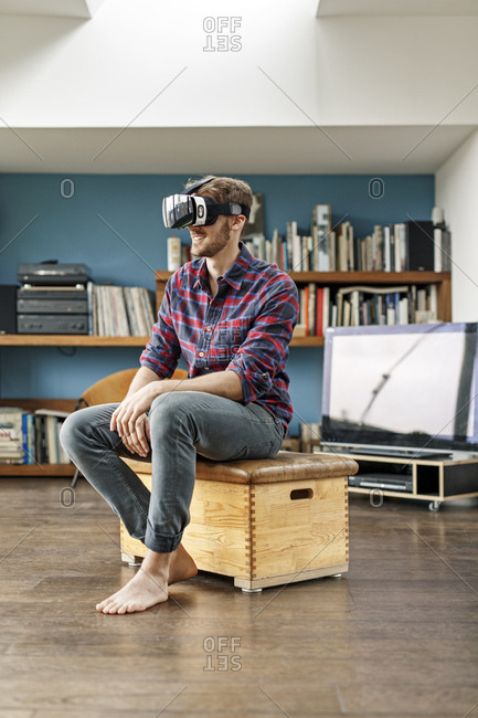 Young man at home sitting on box wearing VR glasses