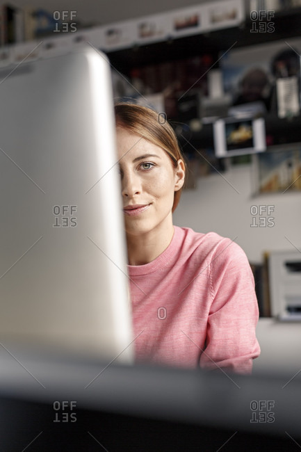 Portrait of young woman behind computer screen at desk at home
