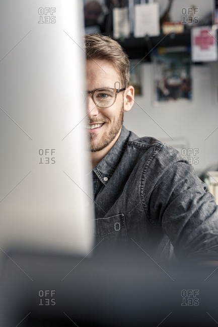 Portrait of smiling young man behind computer screen at desk at home