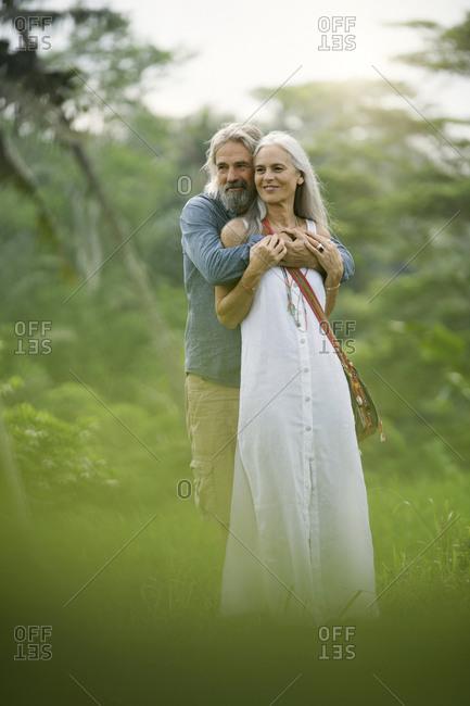 Handsome senior couple hugging in tropical landscape