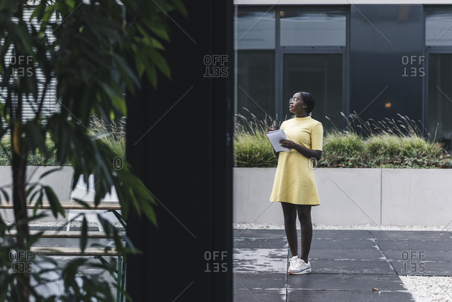 Businesswoman standing outside the office holding notebook