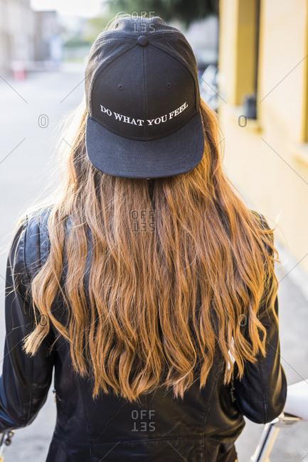 Back view of fashionable young woman wearing black baseball cap