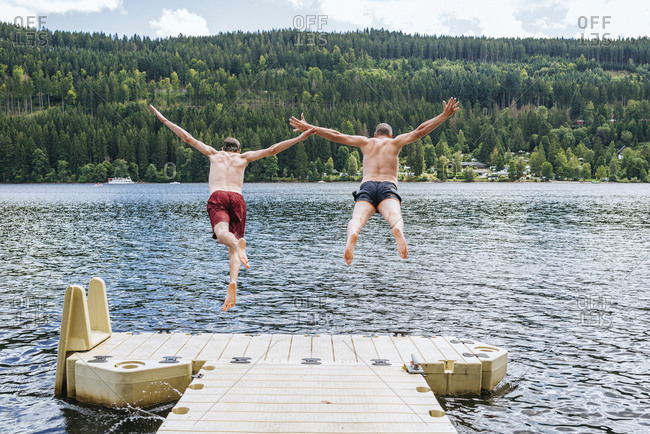 Germany- Lake Titisee- two men jumping into lake from a jetty