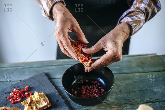 Man's hands peeling a pomegranate