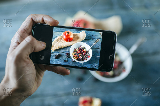 Man's hand taking a picture with smartphone of bowl with dessert of almonds- pomegranate and chocolate