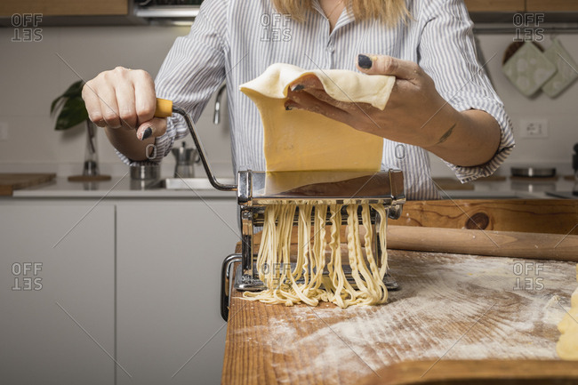 Woman preparing homemade pasta- using pasta maker