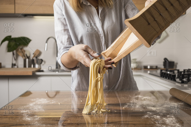 Woman preparing homemade pasta- row noodles- pasta harp