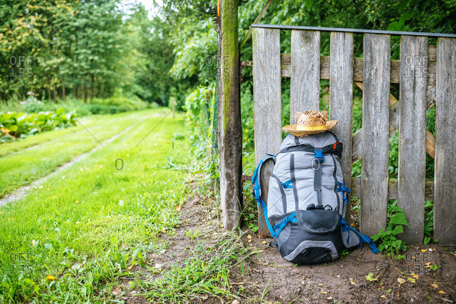 France- Strasbourg- travel backpack and straw hat in front of wooden fence on the way