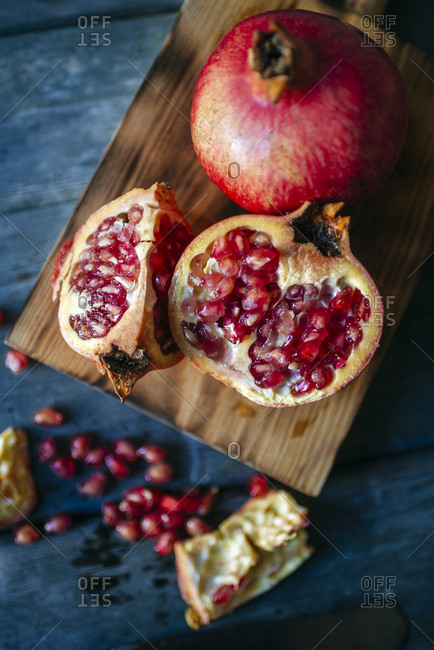 Sliced and whole pomegranate on cutting board