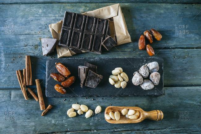 Dates- dark chocolate- almonds- cinnamon sticks  and dried figs on wood