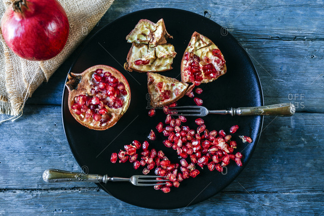 Half of pomegranate- pomegranate seed and two old forks on black plate