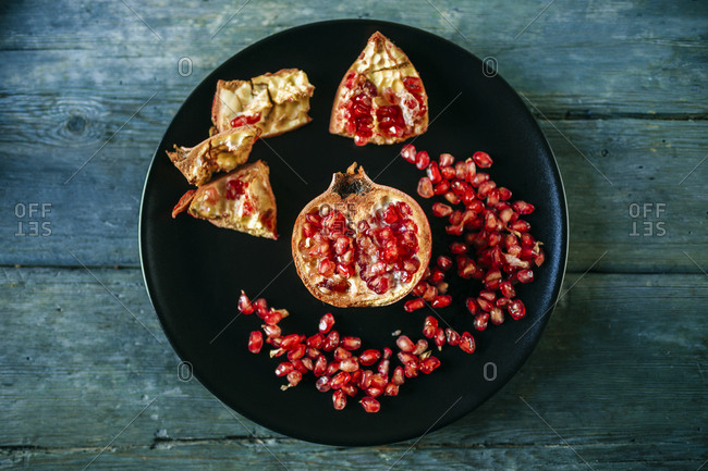 Half of pomegranate and pomegranate seed on black plate