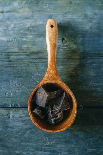 Wooden spoon with dark chocolate pieces on wood