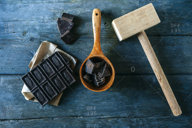 Dark chocolate on paper- wooden spoon and wooden hammer on blue wood