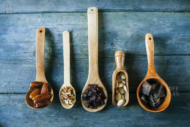 Row of different wooden spoons with dates- walnuts- currants- almonds and dark chocolate