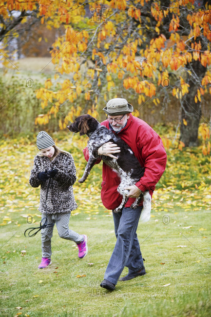 Granddaughter and grandfather walking with dog in park