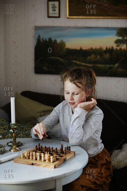 Girl playing chess in living room