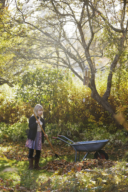 Girl raking leaves in garden
