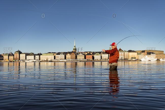 Man fishing in city - Offset