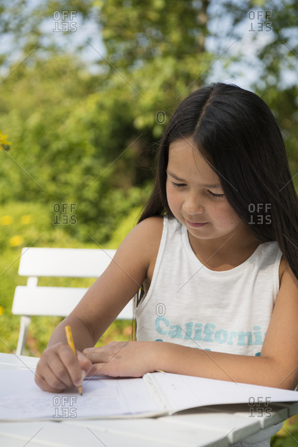 Girl doing homework in garden