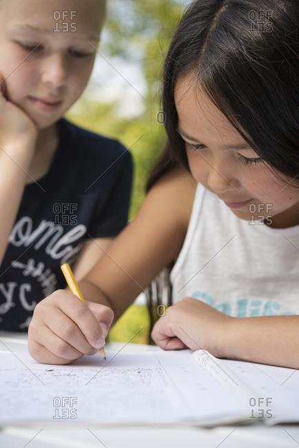 Girls doing homework in garden