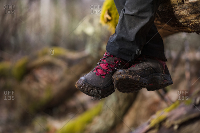 Person in hiking boots sitting, low section
