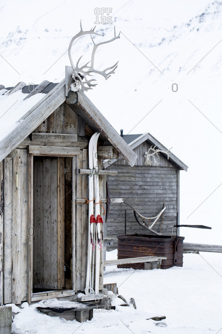 Wooden hut with skis in winter