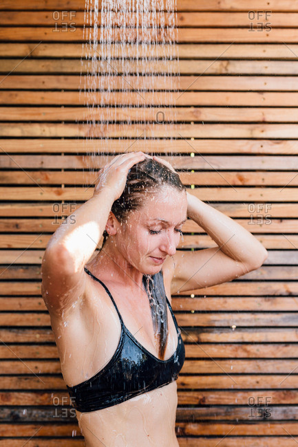 Young woman using outdoor shower