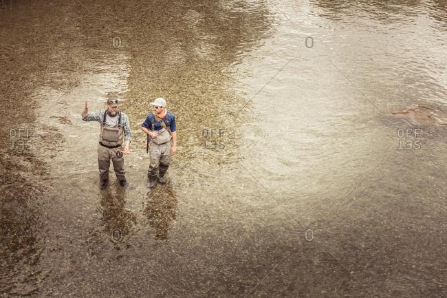 Two fishermen ankle deep in river, Mozirje, Brezovica, Slovenia