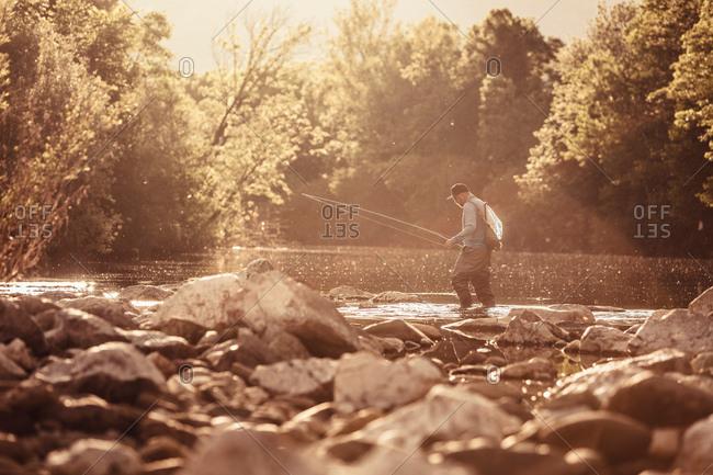 Fisherman ankle deep in sunlit river, Mozirje, Brezovica, Slovenia